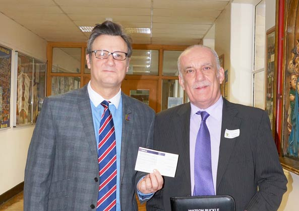 Headteacher Laurence Bentley receives a cheque from Ian M Gill